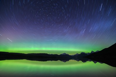 The Aurora Borealis shines across the night sky as the stars swirl above Glacier National Park, Montana. Photography Tip: This photo is a single twenty-five minute exposure. When I shot it, the Northern Lights were just a faint band of color across the sky. If the Aurora had been bright and active at this point in the evening then this long-exposure image would have blown out and failed. The message that I hope to share today is that even a tiny faint light source will slowly become brighter and brighter to the camera if you extend the shutter speed into the seconds, minutes, and hours range. Learn more about my digital photography workshops and Adobe Photoshop Lightroom training opportunities at http://www.davidmarx.com