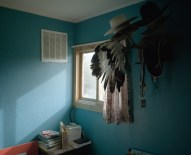 """A war bonnett hangs in the home of Kenneth """"Tuffy"""" Helgesson underneath his collection of cowboy hats, in Lodgepole. Helgesson is an important member of the Assiniboine community; he is one of the few remaining natives who is fully fluent in their language, and is a strong advocate for the continuation of traditional culture. Because of his skills and belief in the importance of maintaining culture, Helgesson is a teacher at the local public high school, where he teaches language and culture classes to future generations."""
