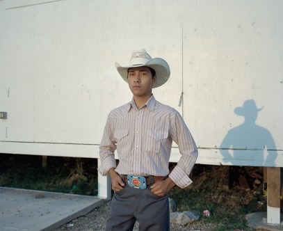 """Dax Wing, 18, stands behind the announcers stand at the Rocky Boy Powwow in Rocky Boy, Montana. Wing is a farmer and cattle rancher who lives on the Ft. Belknap reservation. He is very particular about what he wears, preferring a high-end Western look; sparing no expense on high end cowboy boots or a delicately hand-beaded belt buckle. """"Clothes make the man,"""" he says."""