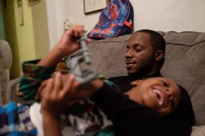 Bronx, NY Oct. 12, 2014 Travis plays with his 5-year-old son. He became a young father at the age of 20 and supports his son through his freelance video production work. He hopes to afford a place of his own one day, but for now lives with his mother and sister. Photo by M.B. Elian