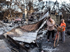 A girl finds her orange bicycle mostly intact with only the seat slightly melted, it had survived the wildfire that had raged through the street and neighborhood where she lived, destroying many homes, on Point Dume ,Malibu California.
