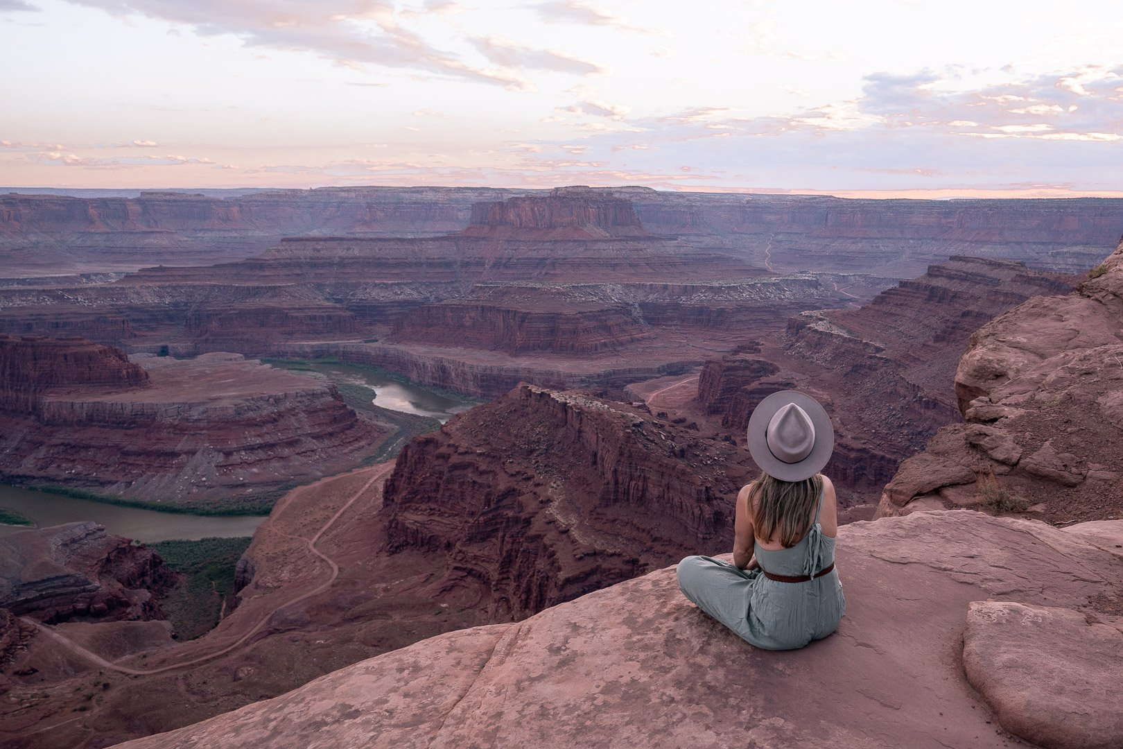 A girl sitting at the edge of a cliff with views of the green river at Dead Horse State Park in Utah
