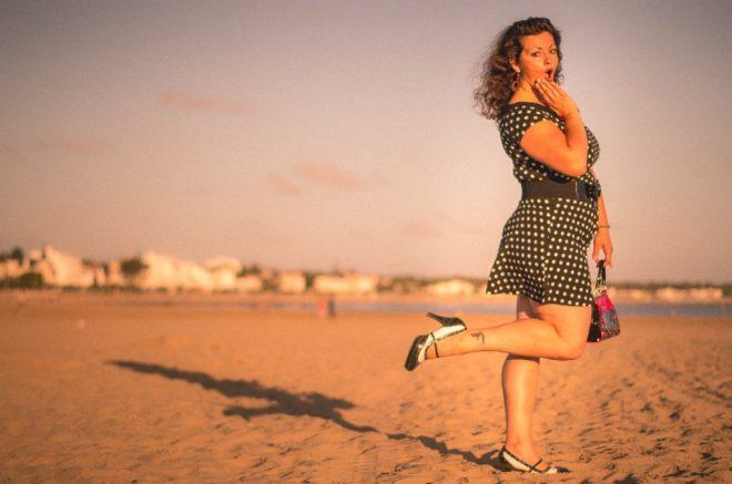 une femme pose en pin-up sur la plage