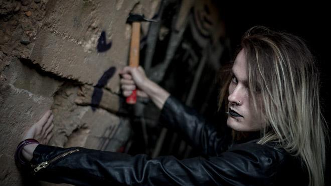 Jeune homme avec un marteau en shooting photographique.