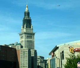Image of Terminal tower against the skyline with the goodyear blimp floating by it.