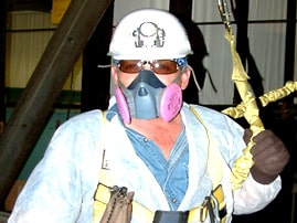 Image of thomarios employee in saftey gear that includes a mask, hard hat, and gloves