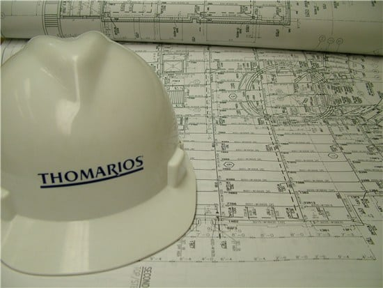 Image of thomarios hard hat laying ontop of blue prints