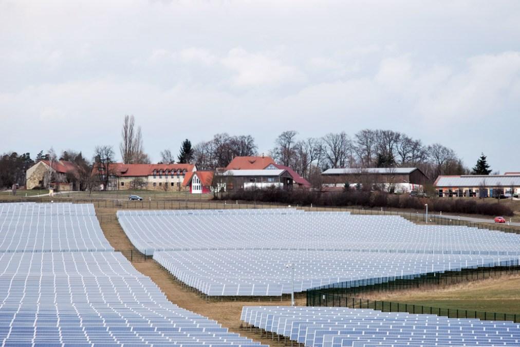 Freiflächen-Photovoltaikanlage vor historischer Gutsanlage.