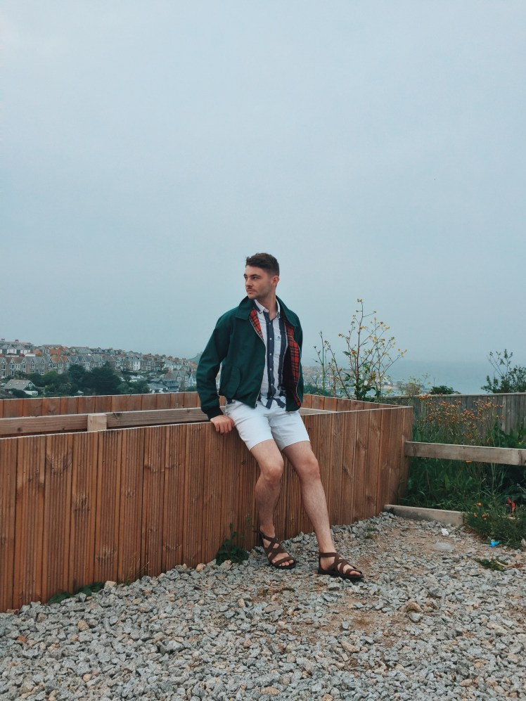 My outfit for the day, white shorts, brown gladiator sandals, a blue and white stripey shirt and green jacket layered on top. This photo shows an overlook from the edge of the car park down to St. Ives below.