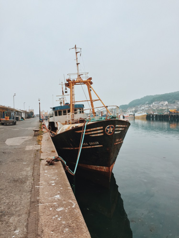 Large rusty fishing boat docked at Newlyn harbour