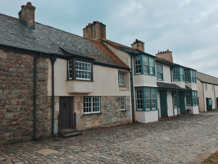 A strip of Cornish houses located in the island harbour of St. Michael's Mount. The buildings are traditional Cornish with a mixture of large stones, painted windows and doors.