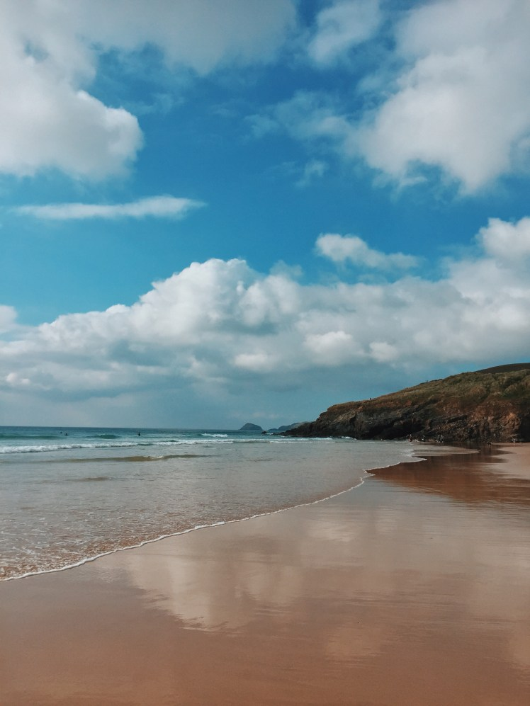 The far end of the beach at Perranporth, where the cliffs fall into the water and the waves are crashing against it. The sky is blue, full of white clouds and brings a summery feel to the picture.