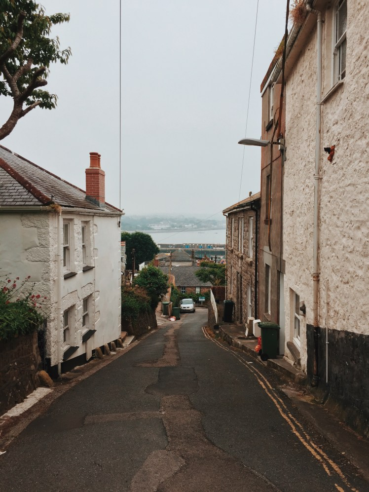 A narrow lane that winds down towards the Newlyn harbour with views of Penzance and the ocean.