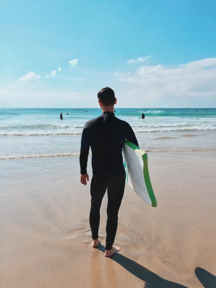 A shot of my boyfriend Jacob with his wetsuit on from the back. He is looking out to the water eager to jump in and learn to ride on the waves. The sky is this magnificant light blue that falls into the turquoise and white water below. The waves are clear as crystal as they lap against the shore.