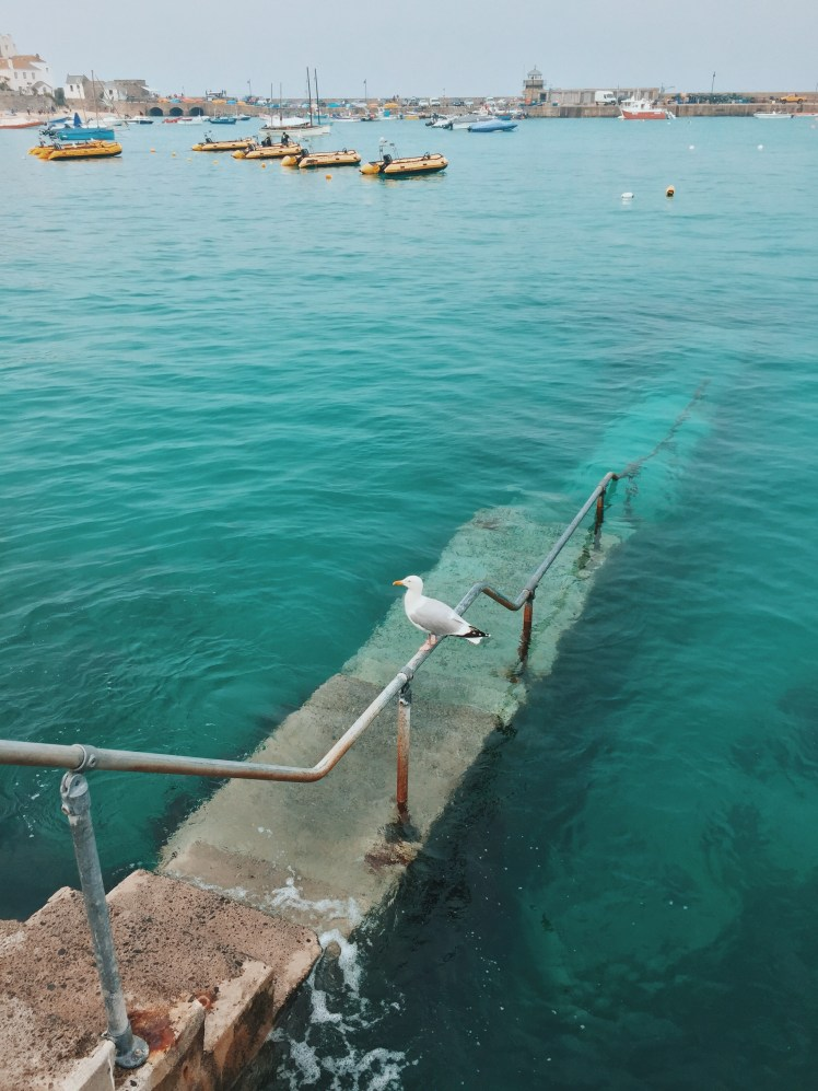 The steps leading into the water at St. Ives port. They submerge and visibility is hazy against the turquoise colour of the water.