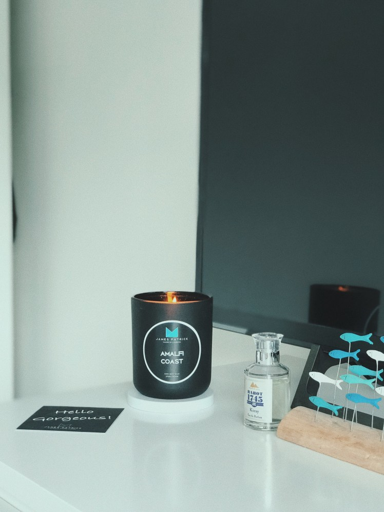 James Patrick Amalfi Coast candle sitting on chest of drawers alongside a little fish sculpture and Rabot 1745 eau de parfum. It is lit and flickering is reflected from the television screen behind.
