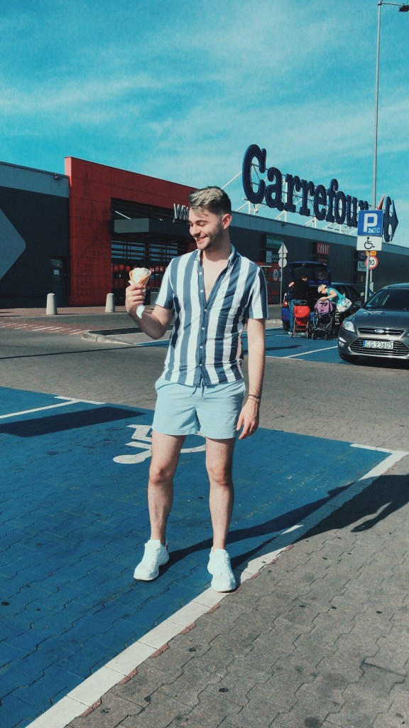 Outside a large mall called Carrefour holding a massive ice-cream cone which cost me next to nothing. Wearing a cute outfit and smiling to life
