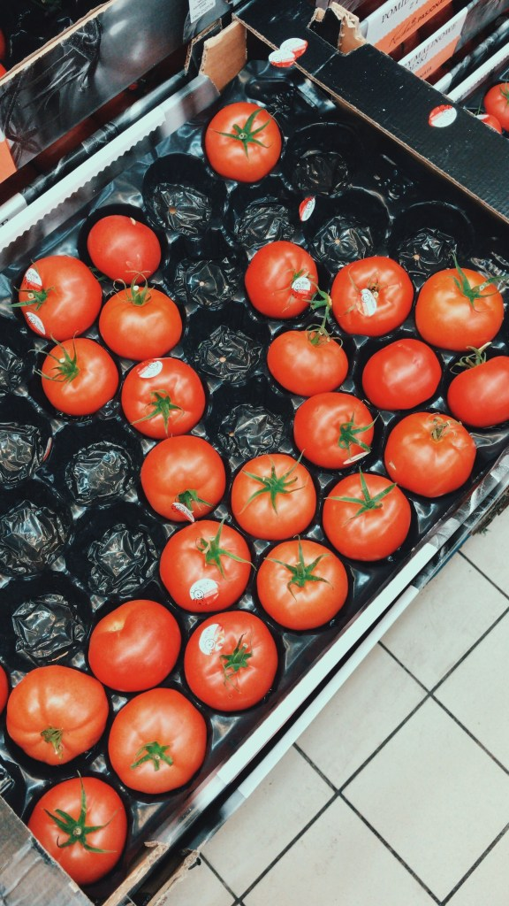 A shot of a tray of large tomatoes at the local grocery store. They are bursting with colour and freshness
