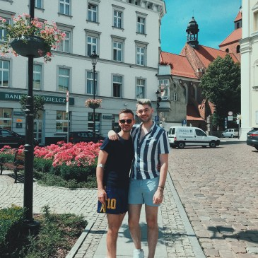 Jacob and I outside in a Polish city. The sun was shining and the flowers behind us bring a burst of colour to the frame. You can see the traditional Polish buildings next to us too.