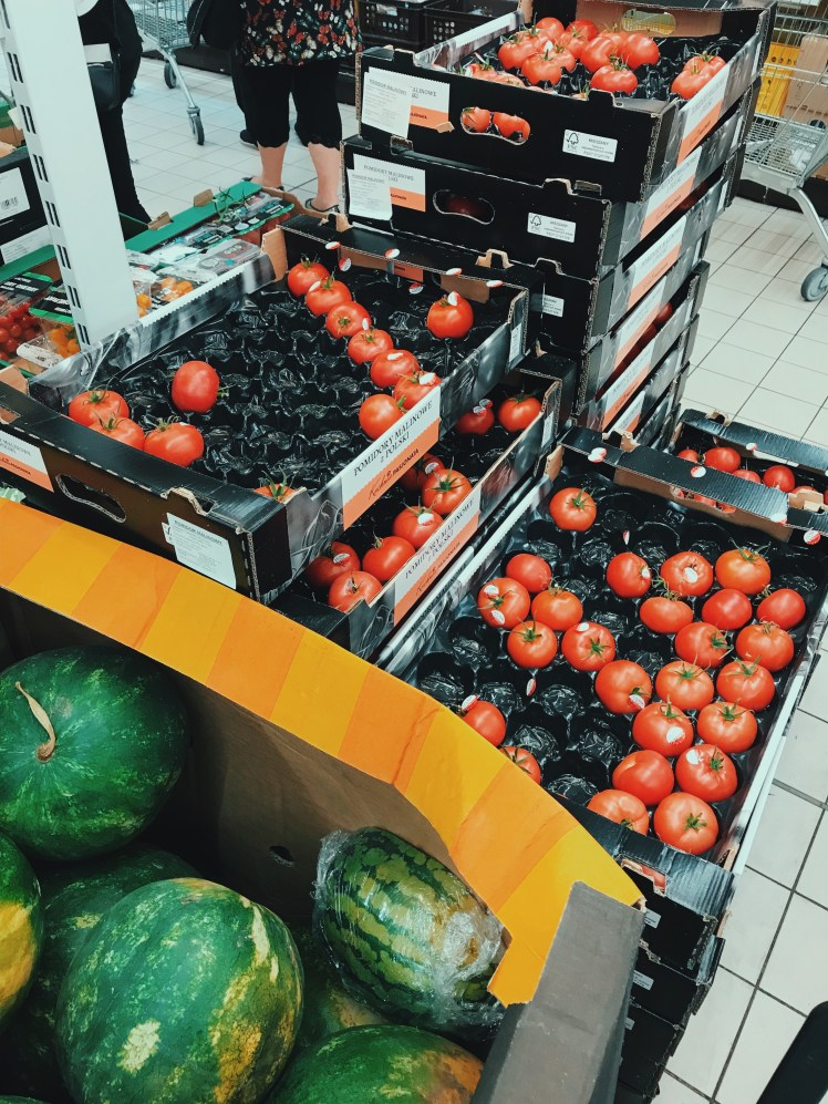Shot of the trays of tomatoes and watermelons avaliable at the grocery store. They were large fruits all full of colours and freshness
