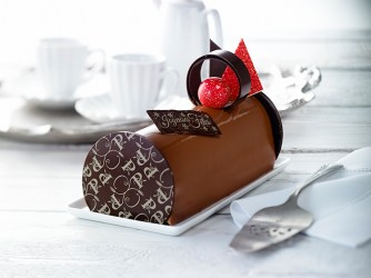 Buche caramel abricot: Biscuit aux noisettes garni de ganache au caramel, crémeux aux abricots, mousse chocolat caramélia (chocolat au lait Valrhona au caramel), le tout recouvert d'un glaçage au chocolat au lait.