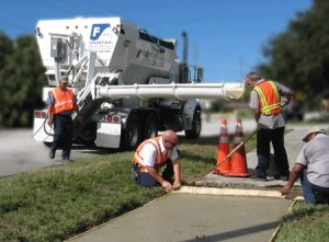 Ready mix truck pouring concrete for sidewalk.