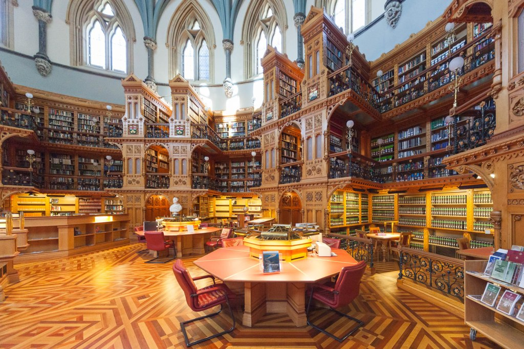 Image of the Library of Parliament in Canada, a neogothic building with tall wooden bookshelves.