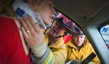 Two firefighters placing a neck brace on a woman injured in a car accident.