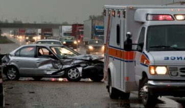 Severely damaged vehicle after an auto accident with an ambulance in the foreground.
