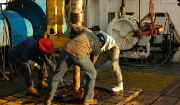 Three oil workers operating a drilling rig