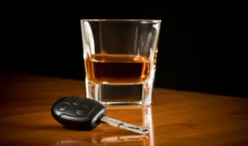 Glass of dark liquor on a table next to a car key.