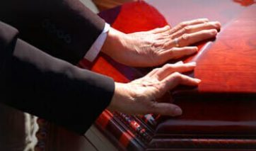 Two people with their hands placed on a casket at a funeral.
