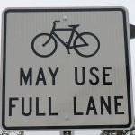 Sign saying bikes can use the full lane.