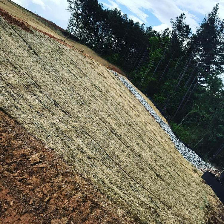 We can help with erosion control on steep slopes! How? We install straw matting.