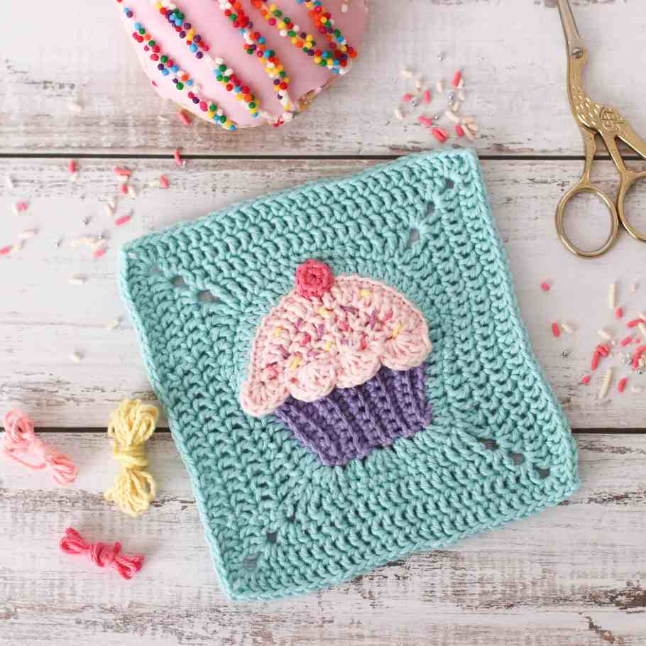 pink crochet cupcake granny square surrounded by sprinkles, yarn and an iced donut