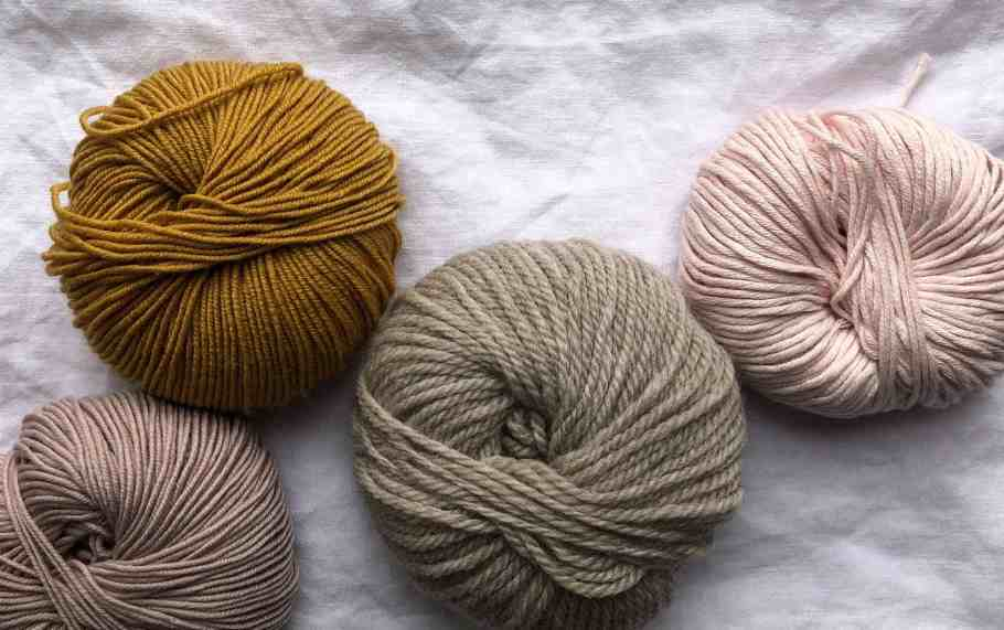 Different color yarns on a white fabric background