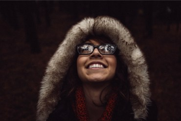 girl-glasses-looking-up-fur-hood-coat-smile-smiling
