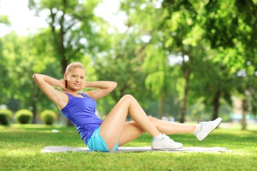 core-workout-abs-muscles-pretty-girl-sports-model-green-grass-trees-turquoise-shorts-white-trainers-tanned-long-legs-yoga-mat-stomach-exercises-crunches