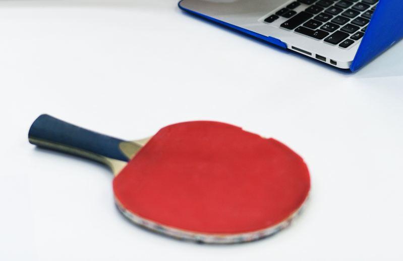 Ping-pong paddle next to laptop