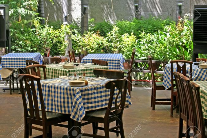 1639664-Outdoor-italian-restaurant-with-chairs-and-tables-with-checked-tablecloths-Stock-Photo