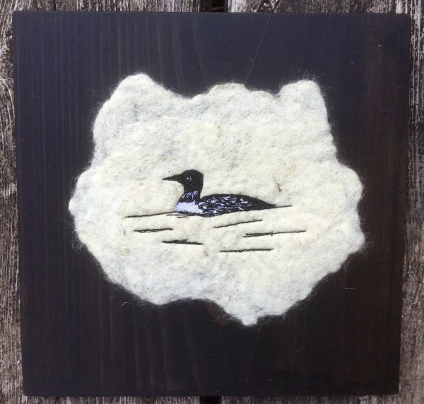 Common loon free motion embroidered on felted fabric on a pine board