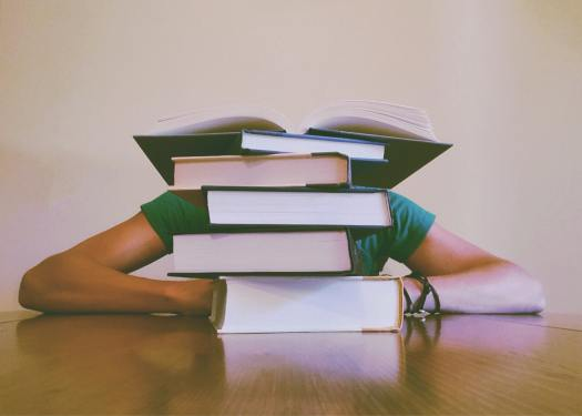 Stack of books with student hiding behind the books.
