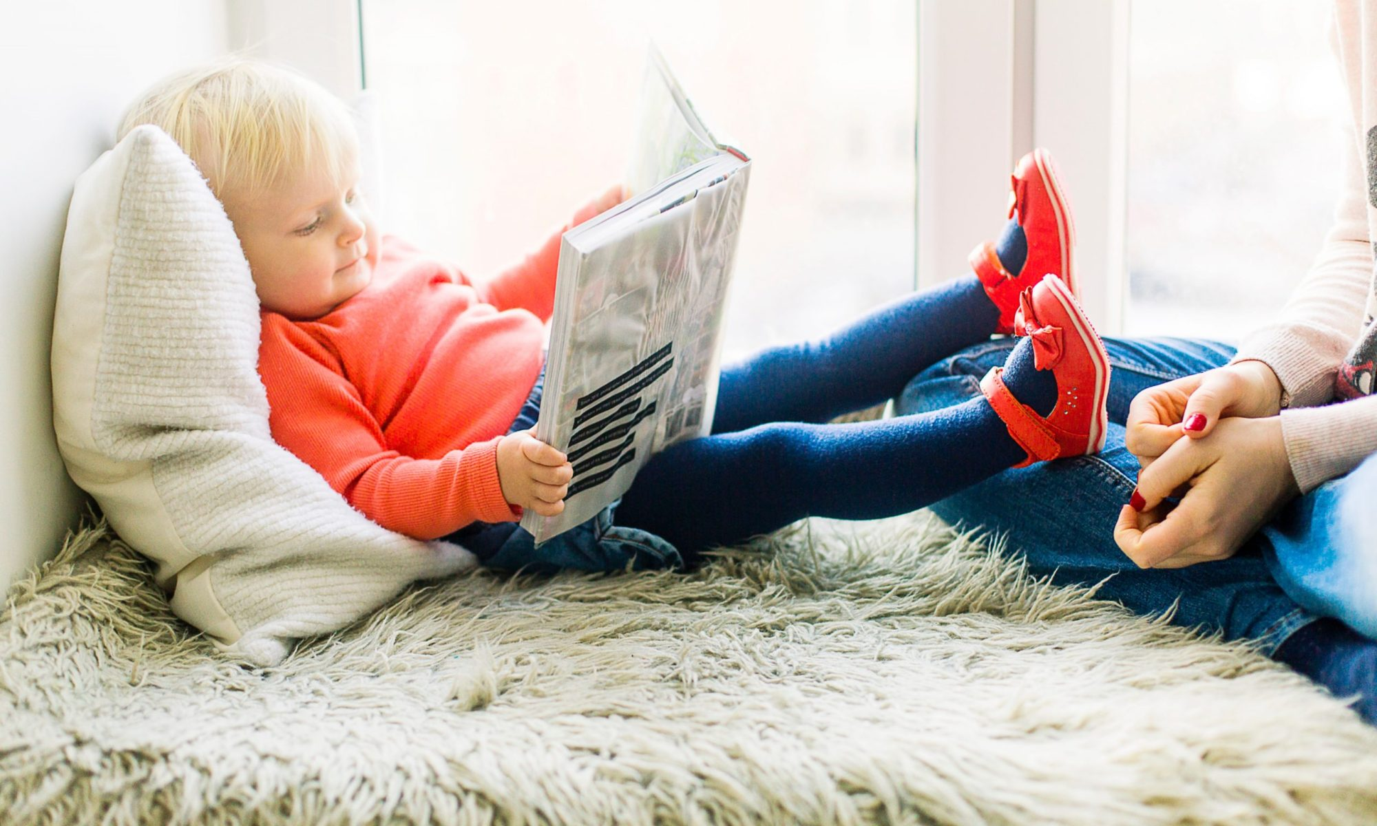 Toddler laying on a bed reading a book with mother sitting nearby.