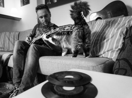 man playing guitar next to cat