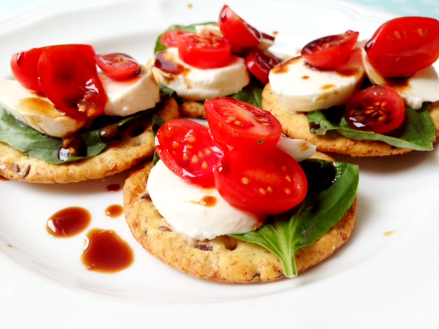 Caprese salad on mulitgrain crackers with balsamic vinegar drizzle