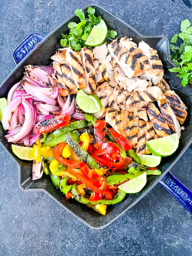 Citrus Chicken Fajitas on the Grill cut up and placed into a skillet with limes
