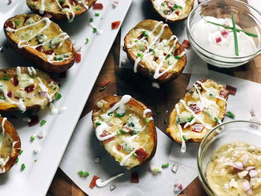 Potato skins on a plate and board with dipping sauces