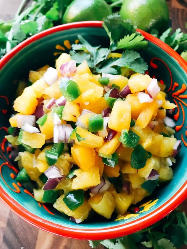 Ready in 10 minutes, this fun and unique salsa is a perfect twist on pico! Great for a cookout, barbecue, party appetizer, and more! Eat it plain or on BBQ chicken or pork for a fun and unique dish. Gluten free, paleo, Whole 30, vegan, vegetarian. Pineapple Serrano Salsa | Three Olives Branch | www.threeolivesbranch.com