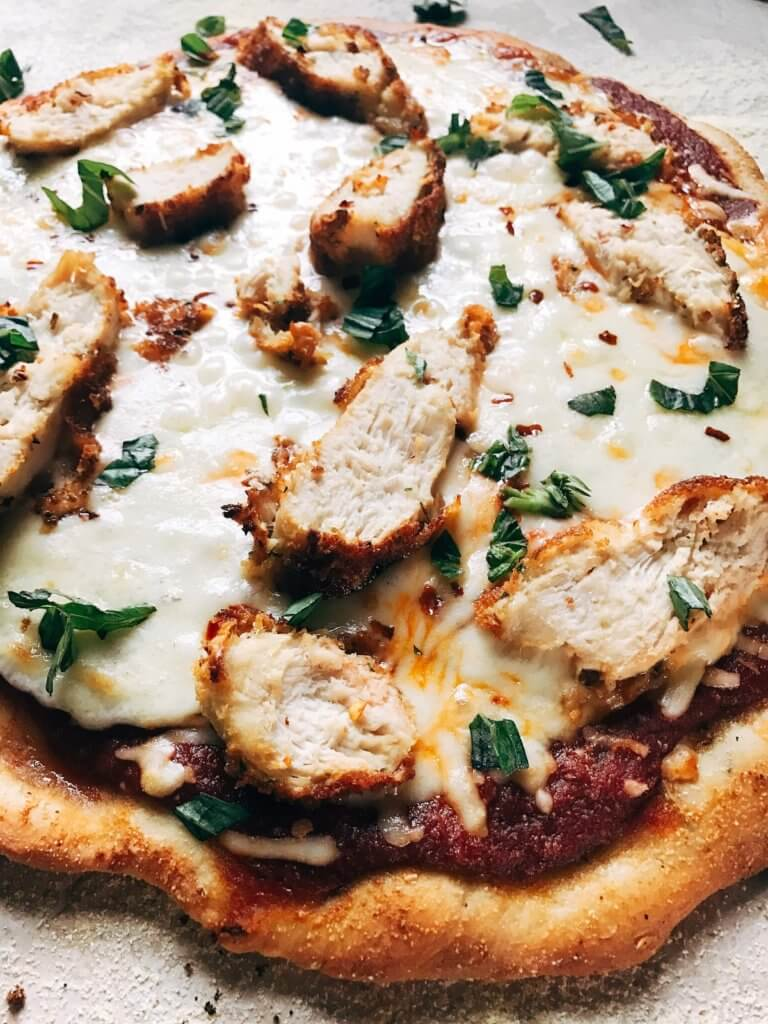This pizza uses classic chicken parm flavors! Make the sauce, chicken, and crust in advance for a quick dinner. The pizza can be pre-made and frozen. Provolone, parmesan, basil, breaded chicken, and a red wine oregano sauce shine on this rosemary red pepper pizza dough. Great for pizza night or parties and entertaining. Chicken Parmesan Pizza | Three Olives Branch | www.threeolivesbranch.com