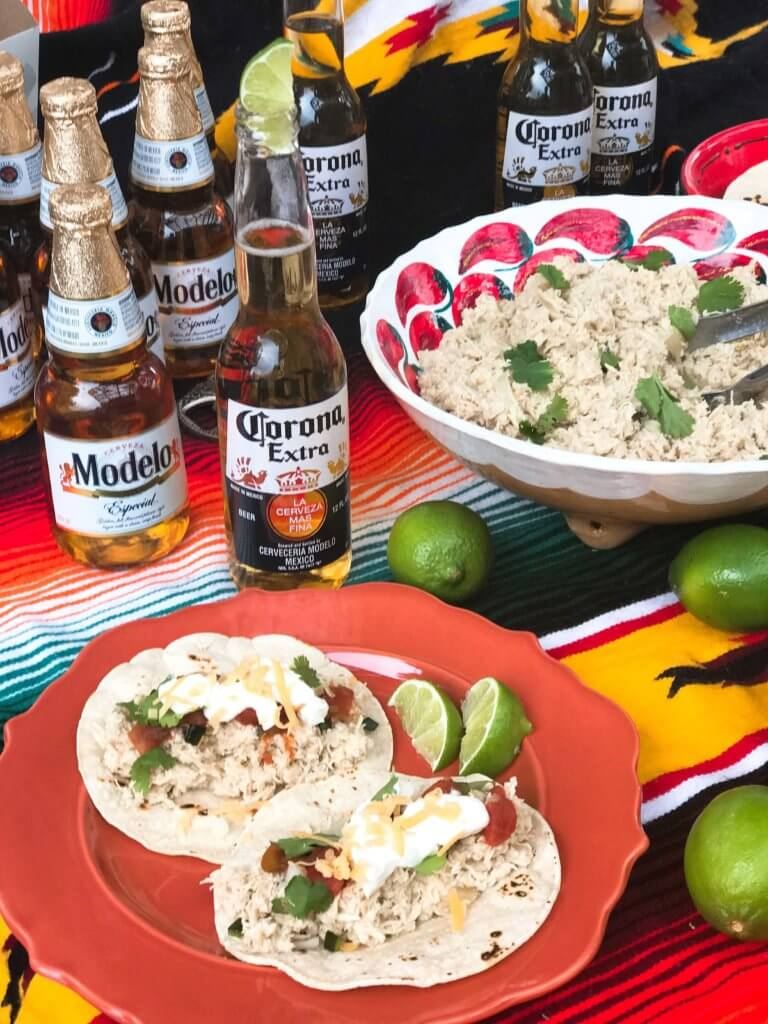 Quick and easy slow cooker chicken is perfect for tacos, enchiladas, and more! Serve it up as an easy taco bar, perfect for your guests and entertaining at parties and Cinco de Mayo. Green chiles, onion, cumin, and Corona beer are a perfect flavor combination for light and delicious tacos or Mexican food. Simple and fast to put together. Slow Cooker Mexican Beer Chicken   Three Olives Branch   www.threeolivesbranch.com
